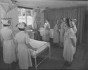 Nurses standing in hospital ward, with two beds an...