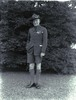 Standing in front of trees, in Scout uniform