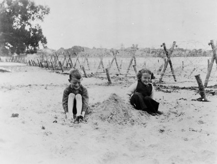 Children on Takapuna Beach with barbed wire. WW2 defence ...