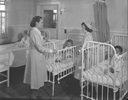 Two nurses standing in children's ward, with two s...