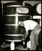 [Mate Ivicevich fills a bottle of Blackberry Nip from a large barrel at Mayfair Wines].