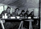 Five soldiers seated at trestle table in marquee e...