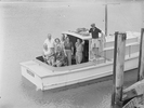 High angle view of eight people on-board a boat. ...