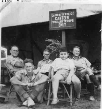 """Group of 4 soldiers and boy sitting in front of tent with sign """"Cairo City Police. Canteen for Allied troops only"""", Jack Lewis (centre back) taken in September 1943 at Mena. - This image may be subject to copyright"""