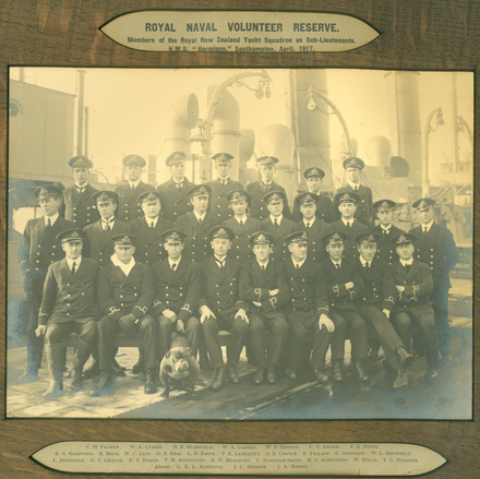 Group Photo, WW1, Royal Naval Volunteer Reserve: members of the Royal New Zealand Yacht Squadron as Sub-Lieutenants. HMS Hermione, Southhampton, April 1917 and their bulldog. Back row left to right C.H. Palmer, W.A. Currie, N.E. Blomfield, W.A. Garden, W.P. Endean, C.V. Brown, F.G. Foote Middle row left to right R.A. Kirkwood, R. Mays, W.C. Leys, G.S. Reid (Hon. Tresurer.), L.N. Foote, T.E. le Huquet, A.E. Choyce, R. Philson, C. Armitage, W.L. Sheffield, Front row left to right - L. Jenkinson, G.T. George, D.V. Hanna, T.M. Alexander, B.W. Beaumont (Hon. Sec.), C. Harrison-Smith, E.C. Alexander, W. Nolan, T.C. Webster Absent - G.E.L. Alderton, J.C. Hewson, J.A. Hardie. - (Copyright © Royal New Zealand Navy Museum. Photo number Hermione 1917. All enquiries for use: https://forms.nzdf.mil.nz/navy/museum/contactform.asp )