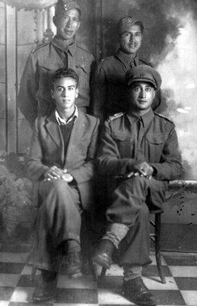 Group, WW2, 3 Maori Battalion soldiers in uniform and one other soldier. Mac Ketenara Tukara is at left rear. Major Henry William Northcroft is on the lower right, in Italy. - This image may be subject to copyright