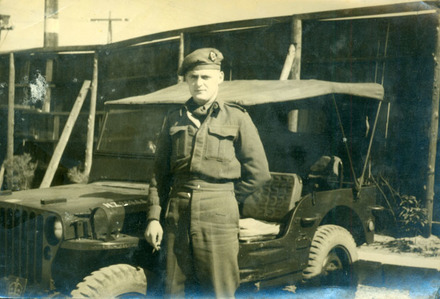 Portrait, WW2, soldier standing in front of jeep, wooden hut, cigarette in hand, wearing beret. Godfrey Perkins 20/641254 at Mizuba 1946 - This image may be subject to copyright