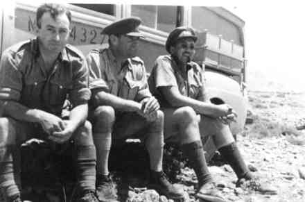 Group, WW2, soldiers leaning against a truck left to right: Frederick Kelly Driver (3532), Major Owen Bracegirdle (3127) and Captain Toogood, Western Desert 1941. - This image may be subject to copyright