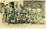 Group, WW2, 18 soldiers posed in front of wooden building, front men hold rifles. Dunstan Ely, Queen Street Official photographer. Soldier 20/641254 Godfrey Perkins, 3rd from right at back, in camp 13 April 1946 (front) - This image may be subject to copyright