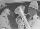 Group, WW2, 2 soldiers, Ron Withell (9274) playing, tries out new euphonium presented by Lieutenant Colonel F. Waite to the 2nd NZEF Base Band at Maadi Camp in Egypt. - This image may be subject to copyright