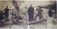 Group, WW1 2 soldiers soldiers and Arabs standing near trees in camp Egypt, 1916 - Windleborn is second from right with cup to his mouth. - No known copyright restrictions