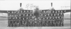 487 Squadron seated under Mosquito, Sculthorpe, October 1943, named men: back row 7th man from left Leith Thompson (pilot); Hugh Mackay (navigator), last man back row Jack Hyndman. Front row 6th man from left Gordon Parks, Wilson O.C. and last man on right Meryn Darrall - This image may be subject to copyright