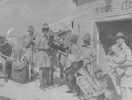 New Zealand Army Band, WW2 holding and unpacking brass instruments outside the Patriotic Store at Maadi, Egypt. Ron Withell (9274) on with a euphonium on right. - This image may be subject to copyright
