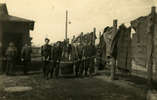 Luckenwalde POW Camp 1945; 4 men carrying large wooden tub on a pole; large pieces of fabric on the fence; group of men facing away near wooden building - This image may be subject to copyright