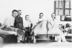 Group, WW1, Visiting an injured soldier in hospital, cot beds, cradle for injured foot, man with jacket is from 4th Waikato Squadron of the Auckland Mounted Rifles, (James Arthur Hunt (7/2275) collection) - No known copyright restrictions