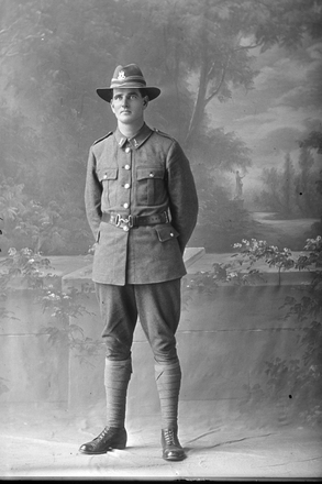 Full length portrait of Private (later Corporal) Leonard Hipkins Clarke, Reg No 46117 of the 25th Reinforcements, E Company. Killed in action in France on the 25th or 26th of August 1918. (Photographer: Herman Schmidt, 1917). Sir George Grey Special Collections, Auckland Libraries, 31-C3067. No known copyright.