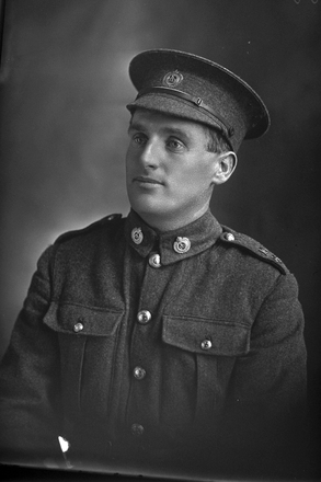 1/4 portrait of Rifleman Ernest James Jackson, Reg No 21023, with the 16th Reinforcements, New Zealand Rifle Brigade, 10th Reinforcements to the 1st Battalion, -  E Company. Killed in action in France, 22 August 1918. (Photographer: Herman Schmidt, 1916). Sir George Grey Special Collections, Auckland Libraries, 31-J1862. No known copyright.