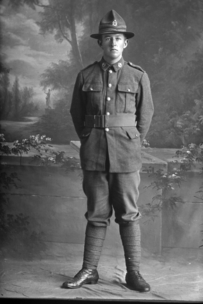 Full length portrait of Private A F Maxwell with the 13th Reinforcements. (Photographer: Herman Schmidt, 1916). Sir George Grey Special Collections, Auckland Libraries, 31-M769. No known copyright.