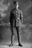 Full length portrait of Corporal George Ambrose Quinlan, Reg No 23314, of the 13th Reinforcements, 7th Reinforcements to the 1st Battalion, New Zealand Rifle Brigade, E Company. In the roll of Honour as a Lance Corporal with the Auckland Infantry Regiment. Killed in action in France on 26 March 1918. (Photographer: Herman Schmidt, 1916). Sir George Grey Special Collections, Auckland Libraries, 31-Q4587. No known copyright.