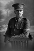 3/4 portrait of Corporal George Ambrose Quinlan, Reg No 23314, of the 13th Reinforcements, 7th Reinforcements to the 1st Battalion, New Zealand Rifle Brigade, E Company. In the roll of Honour as a Lance Corporal with the Auckland Infantry Regiment. Killed in action in France on 26 March 1918. (Photographer: Herman Schmidt, 1916). Sir George Grey Special Collections, Auckland Libraries, 31-Q4588. No known copyright.