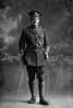 Full length portrait of 2nd Lieutenant Norman Russell Withiel Thomas, Reg No 20940, of the 24th Reinforcements, - E Company, with collar badges of the New Zealand Signal Corps. (Photographer: Herman Schmidt, 1917). Sir George Grey Special Collections, Auckland Libraries, 31-T3276. No known copyright.