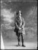 Full length portrait of Colonel James Neil McCarroll, with a moustache, wearing the uniform of the 11th North Auckland Mounted Rifles, campaign medals (Photographer: Herman Schmidt, ). Sir George Grey Special Collections, Auckland Libraries, 31-WP880A. No known copyright.