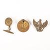 Three metal items: cuff link, button & cap badge.