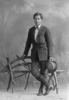 Full length portrait of Mr Mangaroa, standing by a rustic seat, wearing a dark coloured belted jacket, a light coloured shirt and bow tie, dark coloured trousers, long socks, holding a hat. (Photographer: Herman Schmidt). Sir George Grey Special Collections, Auckland Libraries, 31-70945. Image has no known copyright restrictions.