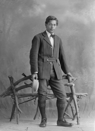 Full length portrait of Mr Mangaroa, standing by a rustic seat, wearing a dark coloured belted jacket, a light coloured shirt and bow tie, dark coloured trousers, long socks, holding a hat. (Photographer: Herman Schmidt). Sir George Grey Special Collections, Auckland Libraries, 31-70944. Image has no known copyright restrictions.