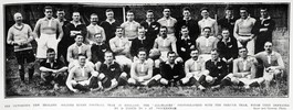 """The Victorious New Zealand Soldier Rugby Football Team in England: The """"All-Blacks"""" photographed with the French team, whom they defeated by 20 points to 3 at Twickenham. Names of the New Zealand team are: - J. O'Brien, P. Story, J. Stohr, J. Ford, J. Ryan, W. Fea, C. Brown, M. Cain, E. Hassell, J. Moffatt, J. Kiswick, E. Belliss, A. West and A. Singe. Taken from the supplement to the Auckland Weekly News 26 June 1919 p037. Sir George Grey Special Collections, Auckland Libraries, AWNS-19190626-37-1. Image ha no known copyright restrictions."""