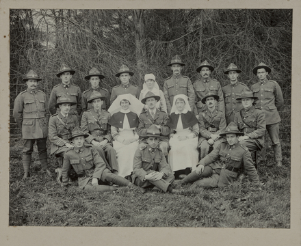 Officers and staff of the New Zealand Section, the Queen's Hospital, Sidcup, 1918. William Henry James Poole far left; Herbert Robert Cole, back row 2nd from left. George William Thomson, back row, 4th from left. Sitting (from left): Captain J.M. Turner NZDC; Captain S.D. Rhind MC, NZMC; Sister McBeth; Major H.P. Pickerill NZMC; Sister Finlayson, Captain AMcP Marshall NZMC; Captain WS Seed NZDC. Isidor Meltzer seated cross legged. Published in Captain Rhind's memoir Plastic Facio-Maxillary Surgery). Auckland War Memorial Museum - Tāmaki Paenga Hira PH-2003-1-67. Image has no known copyright restrictions.