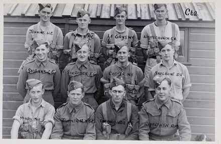 Back row (l-r): W. G. Jenkins, A. C. Burnie, W. B. Le Grys?, E. K. Whitechurch, Middle row (l-r): C. E. Shanks, F. C. Schroder, N. F. Coster, D. R. Sadgrove, Front row (l-r):  N. C. C. McKay, N. W. Johnson, K. E. Amohanga, A. M. Trevarthen. Indentification Album RNZAF (c.1939-1945). Aerodrome Defence Unit, Camp 1. Hibiscus Coast (Silverdale) RSA Museum (G62). CC BY 4.0.