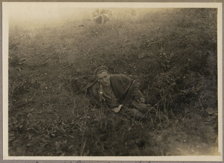A wounded German abandoned by his comrades in a shell hole, waiting for stretcher-bearers who arrived soon after.