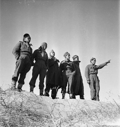 Soldiers of the Maori Battalion study the Tripoli Rd near Azizia (now known as Al Aziziyah), Libya, 10 February, 1943. From left to right: R Reihana (Tu [?]), P Wharepapa (Bay of Plenty), W Johnson (Opotiki), A V Morrison (Ro [?]), J T Harris (North Auckland), T T Daymond (Wellington).