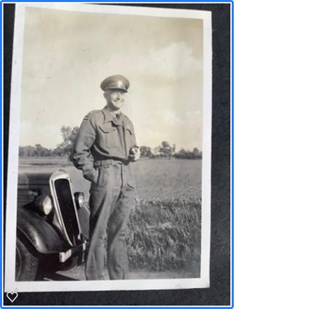 Standing in front of a car in officer's uniform