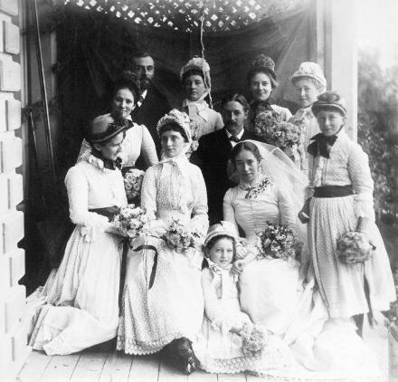 "Alexander Turnbull Library photo caption text reads : ""Wedding party of Dr Walter Fell and Margaret Richmond, 1886 : Reference Number: PA1-q-074-08-1. Wedding party of Dr Walter Fell and Margaret Richmond, in 1886. From left to right, back row: Dr Collins, Emily Richmond, Alice Richmond, Mabel Fell. Middle row: Flora McDonald, Walter Fell, Lil Fell. Front: Ruth Atkinson (kneeling), Mary Richmond, Eva Fell (bridesmaid), Margaret Richmond (bride). Photograph taken by Charles Yates Fell"""