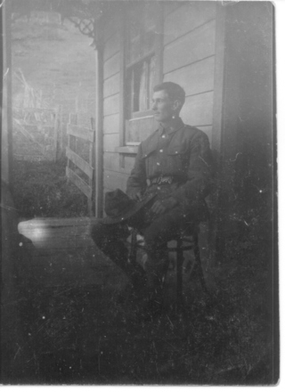 Portrait, seated on verandah of wooden house - No known copyright restrictions
