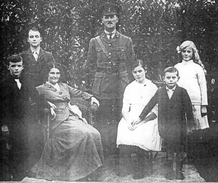 Family group and soldier in uniform photograph taken outside - No known copyright restrictions