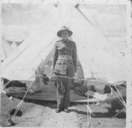 Portrait, standing to attention outside tent, folded blankets, bedding and floor of tent visible, this photograph was either taken in Military camp in New Zealand or in Camp in Egypt. - This image may be subject to copyright