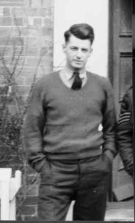 Portrait, standing outside, wearing jumper and tie, hands in pockets - This image may be subject to copyright