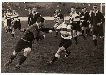 Ken Moses wearing black and holding the ball playing for Kings College against Auckland Grammar School in rugby (kindly provided by family) - This image may be subject to copyright