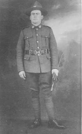 William Baker standing, in uniform, holding gloves - No known copyright restrictions