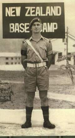 "Photograph of Thomas James Herlihy standing beneath sign ""New Zealand Base Camp"", Korean War. Image is subject to copyright restrictions."