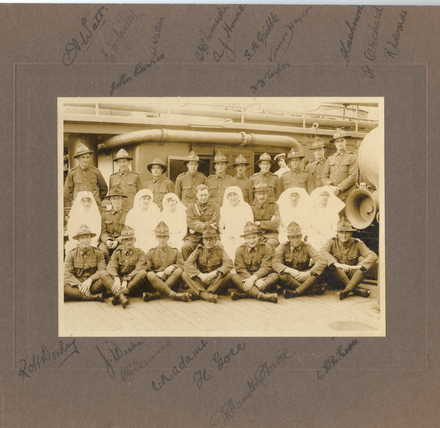 Group, 27 Reinforcement Medical Corps and nurses of the New Zealand Army Nursing Service, photographed on deck. Autographed by 19 of the twenty men in the 27 Reinforcement Medical Corps. The top row has Alexander Watt, Edward McGinley, William Wallace, Stanley Chirnside, Arthur Howes, Stanley Gribble, Vernon Haydon, Alfred Cashmore, Frederick Orchard, Robert Edwards. The second row has Vieira Currie and Harold Herbert Taylor. The bottom row has Robert Dowling, W.J. Weeks, Charles Fenwick, Charles Nightingale Adams, Harry Gore, Adam Harvie and Cecil Howe. Captain Kenneth MacKenzie has not signed the photograph. The nurses are part of the New Zealand Army Nursing Service; it is highly likely that the nurses are Flora Gray, Beatrice Gubbins, Nan Heath, Ruby Millar, Dorothy Miller, Edith Thomson. Nurses, left to right Ruby Millar, Dorothy Miller, Edith Thomson. Beatrice Gubbins sits third from the right. Flora Gray sits first from the right. - No known copyright restrictions