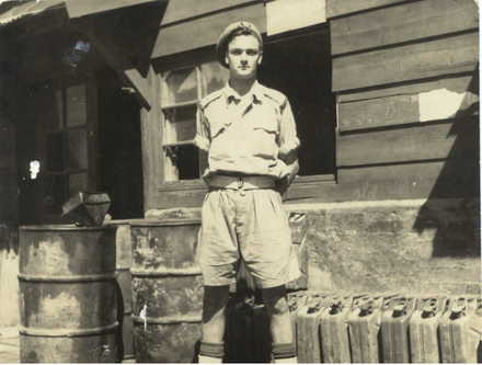 Portrait, standing outside hut with fuel drums and cans lined up beside him - This image may be subject to copyright