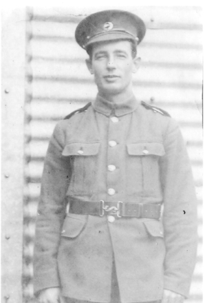 Portrait, WW1, Thomas Donald McConnell 17/339, soldier standing in front of [corrugated] wall, cap, belt and buckle - No known copyright restrictions