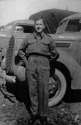 Bernard Arnold Bisphan leaning against vehicle - This image may be subject to copyright