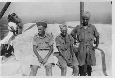 Group, WW2, 3 soldiers, Maurice French (centre) on top of the Pyramid at Giza, soldier in uniform with turban, soldier in white( shorts) and in background soldier and a woman (photo provided by Maurice French) - This image may be subject to copyright