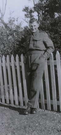 Portrait, Ronald McNaughton standing leaning against a picket fence, hands in pockets - This image may be subject to copyright