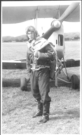 Portrait, full length, John Rhodes aged 18 1944 (front) flight dress including goggles, standing on grass in front of plane - This image may be subject to copyright